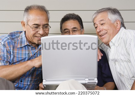 Three elderly men with laptop - stock photo