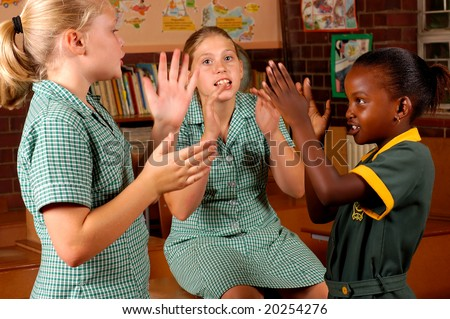 Three elementary girls playing games in a classroom - stock photo