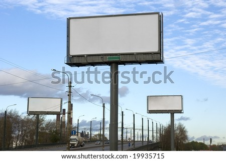 Three empty billboards  along the road. - stock photo