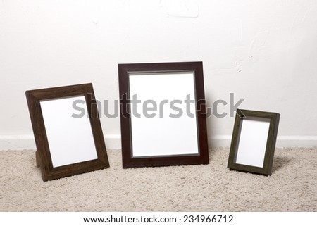 Three empty(blank) photo(picture) wood frames on the ivory carpet at the studio. - stock photo