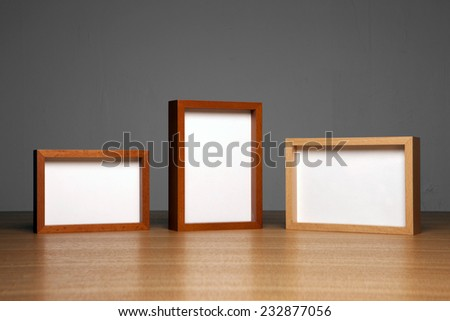 three empty(blank) wood photo frames(teak, cherry, oak) on the wood table(desk) at the studio.
