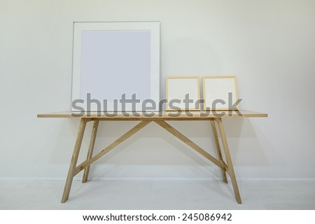 Three empty decorative frame for paintings or photographs on the oak table. Minimalism. Style loft. - stock photo