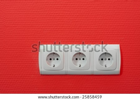 Three empty electric sockets on red wall - stock photo
