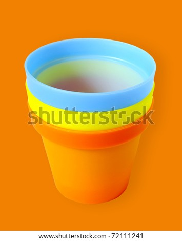 Three empty flower pots isolated on the orange background.