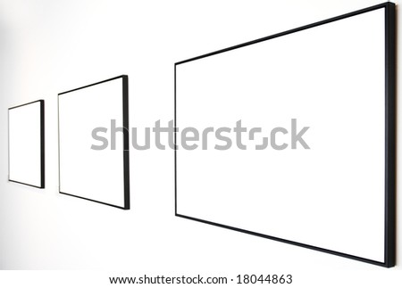 Three empty frames on white wall in museum - stock photo