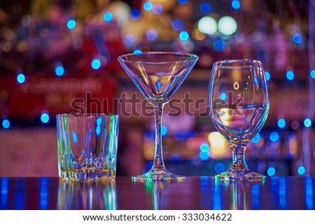 three empty glasses (martini, cocktail, whiskey) on the wooden bar on the background circular bokeh neon lights garland - stock photo