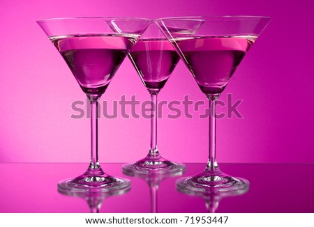 Three empty martini glasses on purple background - stock photo