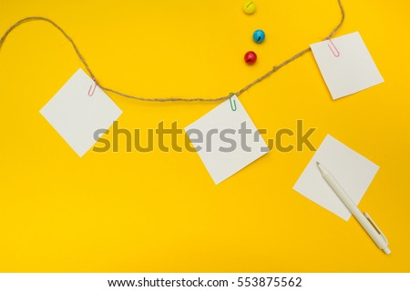 Three empty note papers attached to a rope on a yellow background.