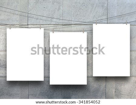 Three empty paper sheet frames hanged by pegs on blue metal sheet background - stock photo