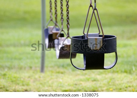 Three empty swings after a summer rain.  Focus is on the first swing.  Envisioned as a metaphor for growing up and putting away the toys of childhood.