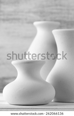 Three empty white unglazed ceramic vases on white wooden table against rustic wooden wall. Black and white image. Shallow DOF, focus on front small vase. - stock photo