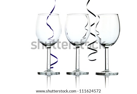 Three empty wine glasses and party streamers backlit against white background - abstract. - stock photo