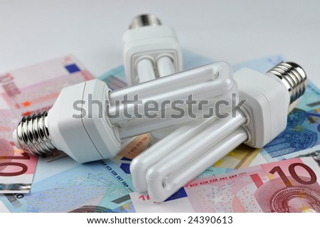 Three energy saving light bulbs on money - stock photo