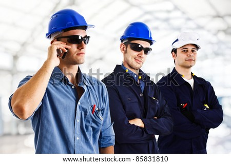 Three engineers at work in a construction site - stock photo