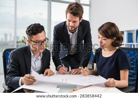 Three engineers examining blueprint of a new project - stock photo