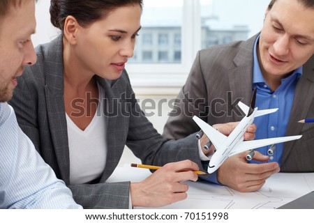 Three engineers looking at a small model of a plane - stock photo