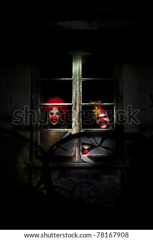 Three Evil Looking Clowns Peering Out The Window Of A Shadowy Building - stock photo