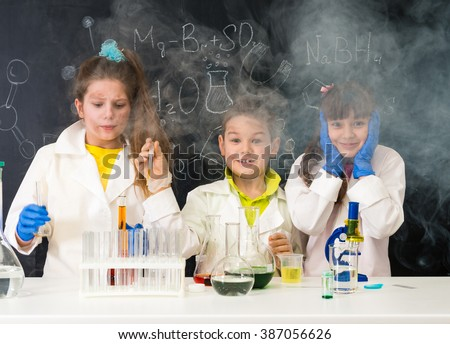 three excited funny children after chemical experiment in lab - stock photo