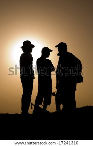 three explorer silhouettes on the top of a mountain