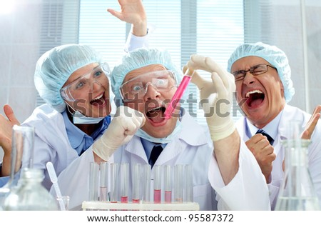 Three extremely emotional scientists being happy about the result of the experiment - stock photo
