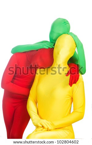 Three faceless people wearing bright, colorful body suits.  Red, green and yellow.