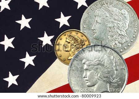 Three faces of Liberty, stars and stripes background. From the top: Morgan silver dollar, gold 5 dollar Liberty Half Eagle, silver Peace dollar - stock photo