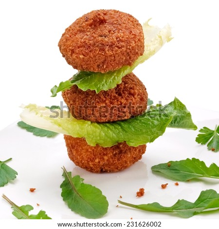 Three falafels with leafs of parsley and lettuce - stock photo