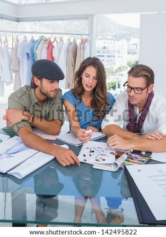 Three fashion designers during a brainstorming in a bright office - stock photo