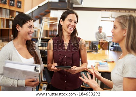 Three Female Architects Chatting In Modern Office Together - stock photo