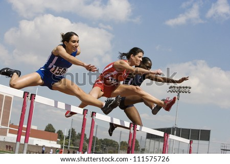 Three female athletes clearing hurdles in race - stock photo