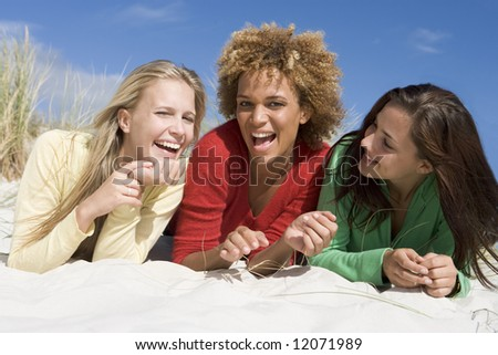 Three female friends having fun at beach - stock photo