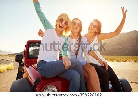 Three Female Friends On Road Trip Sit On Car Hood - stock photo