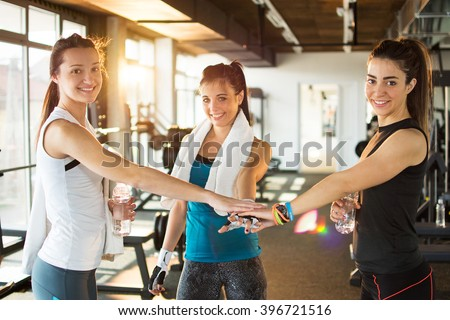 Three female friends putting hands together at the gym. - stock photo