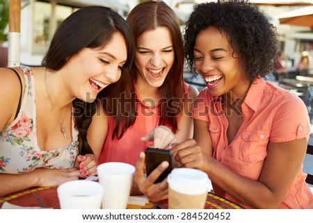Three Female Friends Reading Text Message In Caf\x81_ - stock photo