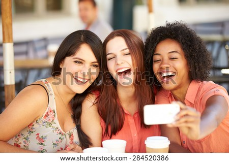 Three Female Friends Taking Selfie In Cafx81_