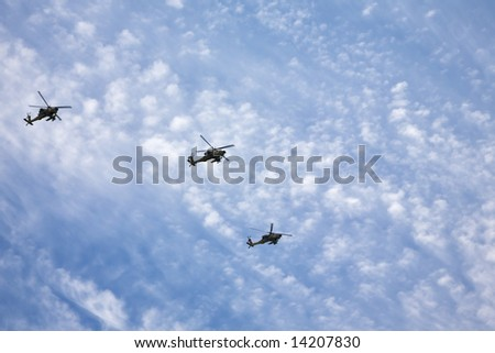 Three fighting helicopters beautifully flying on military-air parade in the cloudy sky - stock photo