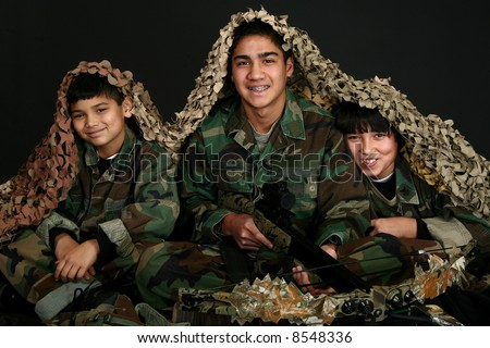 Three Filipino brothers in camo fatigues with crossbow and hunting gear. - stock photo