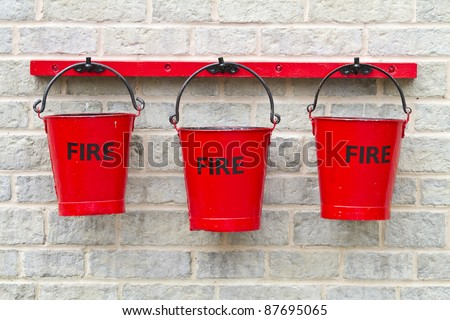 Three fire buckets hanging on a wall - stock photo