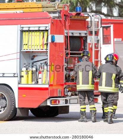 three firefighters and fire trucks during an emergency - stock photo