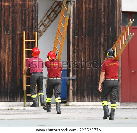 three firefighters during the fire drill mount fast wooden ladder - stock photo