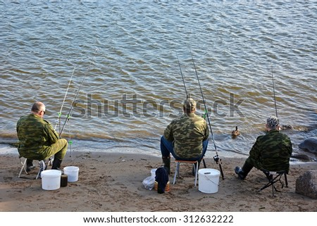 Three fishermen on the sea try to catch fish fish - stock photo