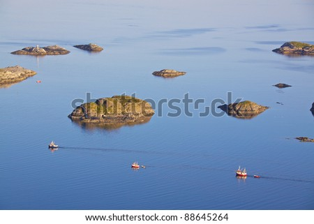 Three fishing boats sailing out to the open sea near Henningsvaer, Norway