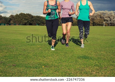 Three fit young women are running on the grass in a park - stock photo
