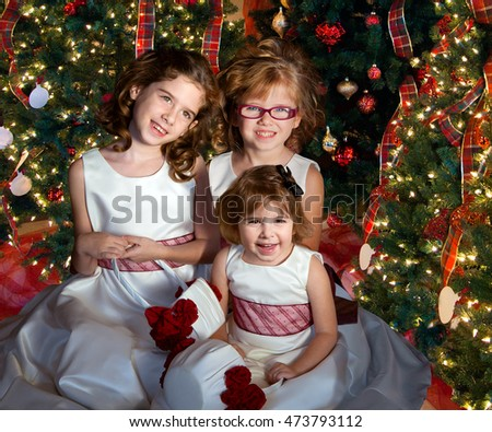 Three flower girls pose for a Christmas picture in the midst of decorated trees.  They are wearing white dresses with red ribbons.