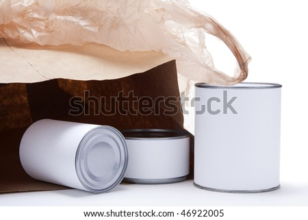 Three food cans with blank white labels in front of an open brown paper grocery bag with a brown plastic shopping bag on top. - stock photo