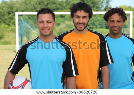 Three football players standing in front of goal