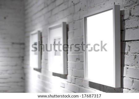 Three frames on white wall in museum - stock photo