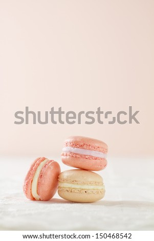 Three French macaron (pronounced macaroon, a popular buttercream filled meringue type cookie or biscuit) in a stacked formation, on white wood table with lace placemat on a soft pink background.