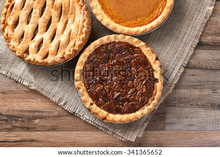 Three fresh baked Thanksgiving desserts, Pecan, Apple and Pumpkin pies seen from a high angle on a burlap and wood surface.