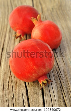 Three fresh red pomegranate on a wooden board - stock photo